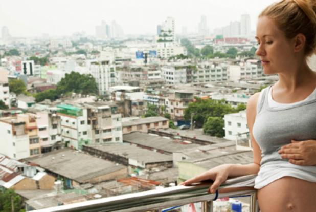 Femme enceinte sur son balcon devant une ville