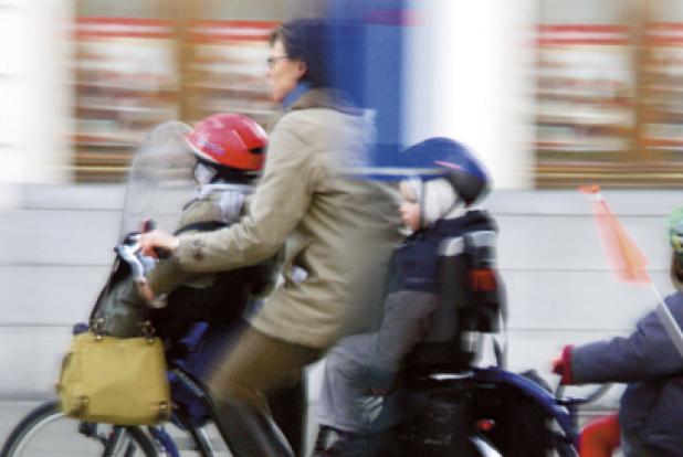 Femme sur un vélo avec ses 3 enfants