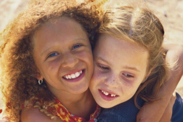 Deux fillettes : une blanche, une noire, qui se tiennent par le cou