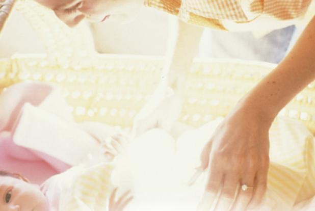 Maman qui se penche sur le berceau de son bébé