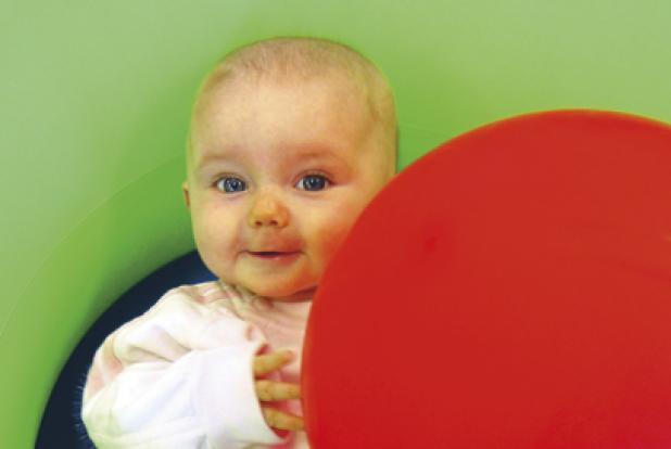 Bébé avec un gros ballon rouge