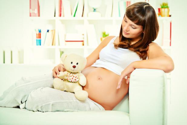 une femme enceinte chez elle attend son bébé