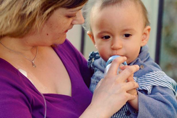 Maman qui porte son bébé dans les bras et luidonne son biberon