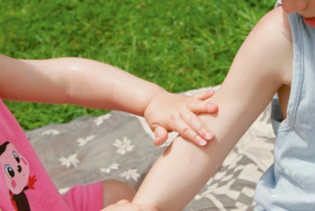 Fillette qui touche la peau du bras d'un petit garçon