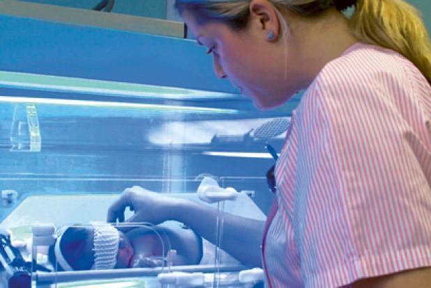 Bébé sous une lumière bleue avec infirmière à ses côtés