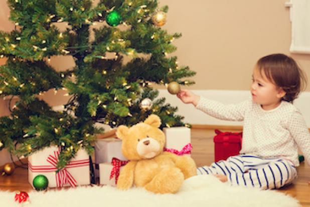 Un enfant devant un sapin plein de cadeaux : l'ours en peluche est une bonne idée de cadeau de noël