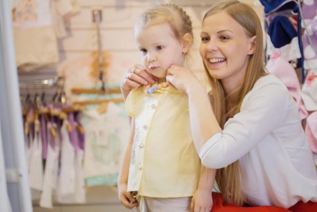Une petite fille essaie des vêtements dans un magasin.