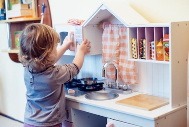 Bebe joue à faire comme les grands dans une petite cuisine