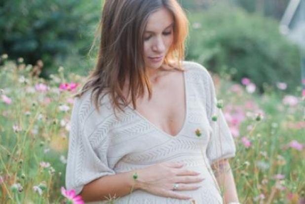 Une femme enceinte en robe dans un champ de fleurs.