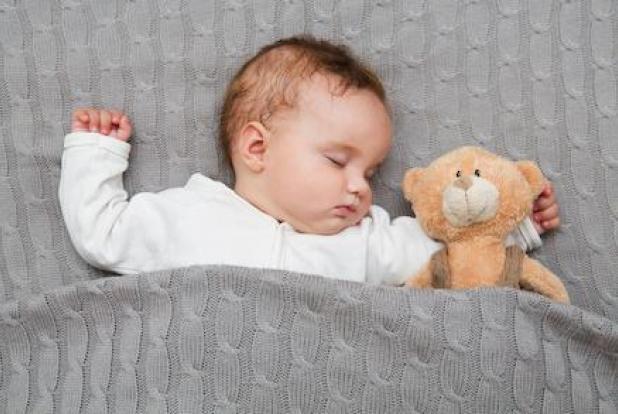Un bébé qui dort à côté de son ours en peluche.