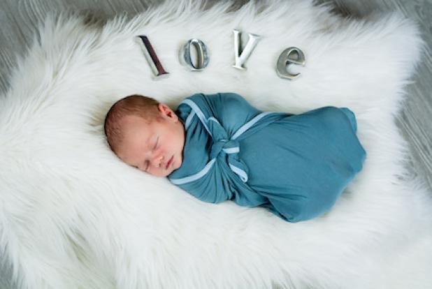Un bébé emmailloté accompagné du mot LOVE