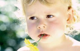 Fillette avec une fleur dans la bouche