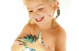 Une petite fille joue avec de la peinture sur les mains