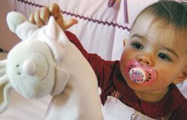 Enfant suçant une tétine qui tend son doudou