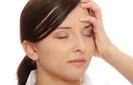 femme enceinte qui se tient la tête en fermant les yeux