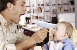 papa nourrisant son enfant avec un petit pot