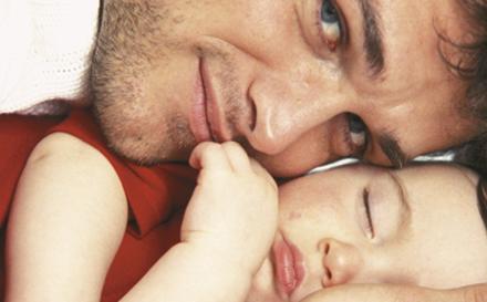 Papa qui cajole son enfant endormi