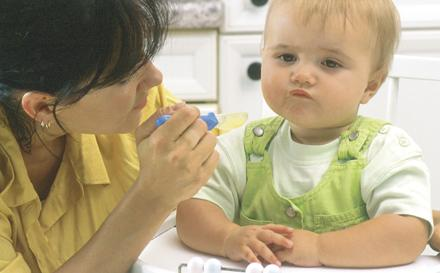 Maman qui essaye de faire manger son enfant