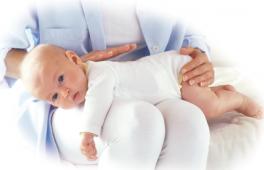 un bébé qui souffre de coliques est allongé sur le ventre sur les genoux de sa maman