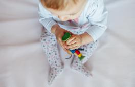 Un bébé tient un jouet dans ses mains
