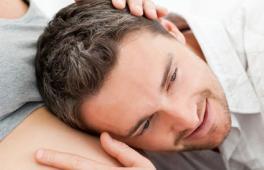 Homme qui pose l'oreille sur le ventre de sa femme enceinte