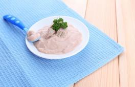 une purée de courgette et veau décorée de persil dans une assiette pour bébé avec une cuillère