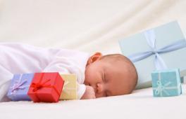 Un bébé endormi entouré de cadeaux offerts à l'occasion de sa naissance.