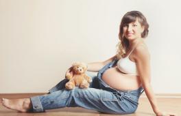 Une femme enceinte assise par terre vêtue d'une salopette.