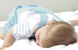 Enfant tout habillé endormi sur le lit de ces parents