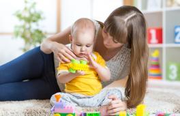Une femme allongée sur le sol est en train de jouer avec un bébé