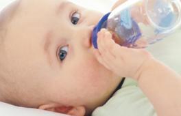 Bébé qui boit un biberon d'aeu