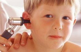 Médecin qui examine l'oreille d'un garçon à l'aide d'un otoscope