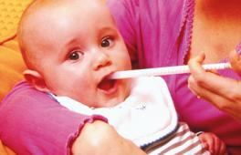 Enfant qui prend un médicament à l'aide d'une seringue