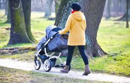 Une femme promène son enfant en manteau et bonnet