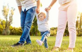 un bébé au parc entre son papa et sa maman