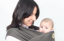 Une maman porte son bébé dans une couverture de portage